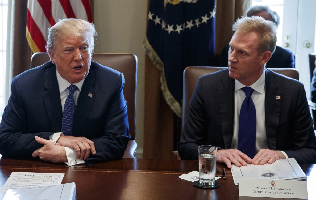 FILE - In this April 9, 2018, file photo, Deputy Secretary of Defense Patrick Shanahan, right, listen as President Donald Trump speaks during a cabine...