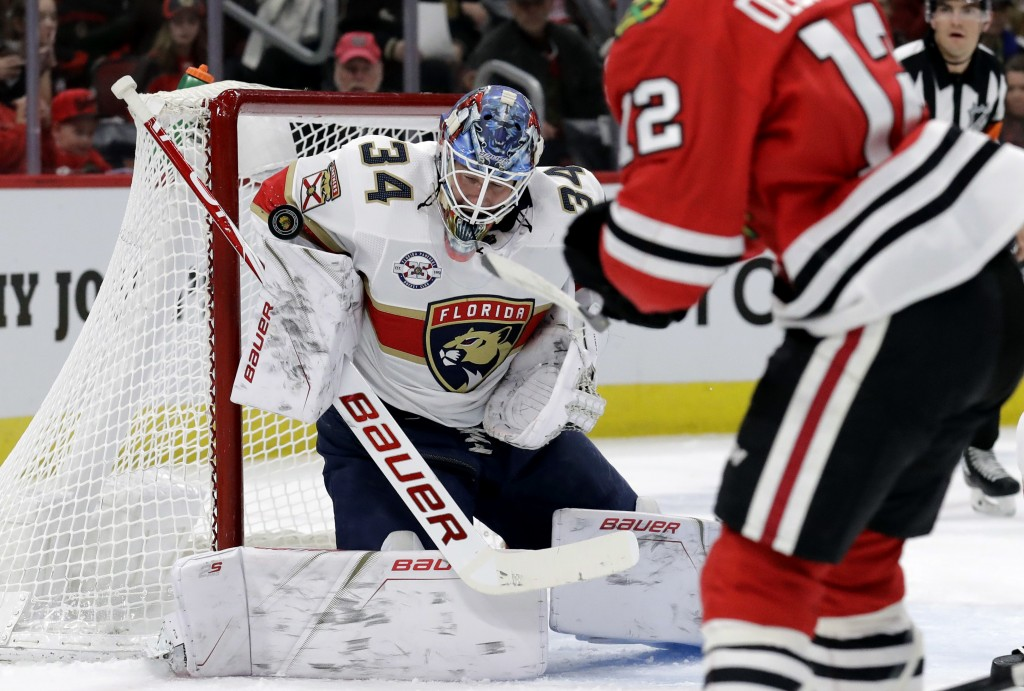 Florida Panthers goalie James Reimer (34) blocks a shot by Chicago Blackhawks left wing Alex DeBrincat (12) during the first period of an NHL hockey g