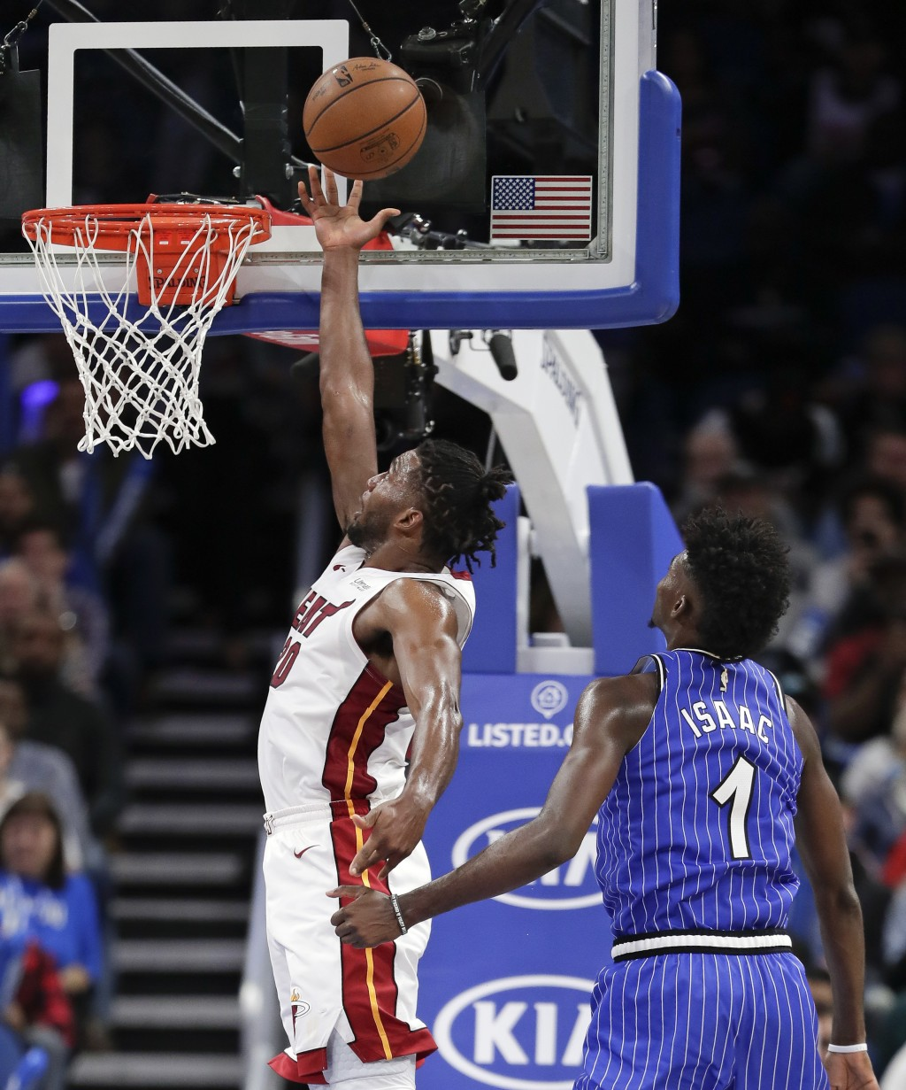 Miami Heat's Justise Winslow, left, goes past Orlando Magic's Jonathan Isaac (1) for a basket during the second half of an NBA basketball game, Sunday...