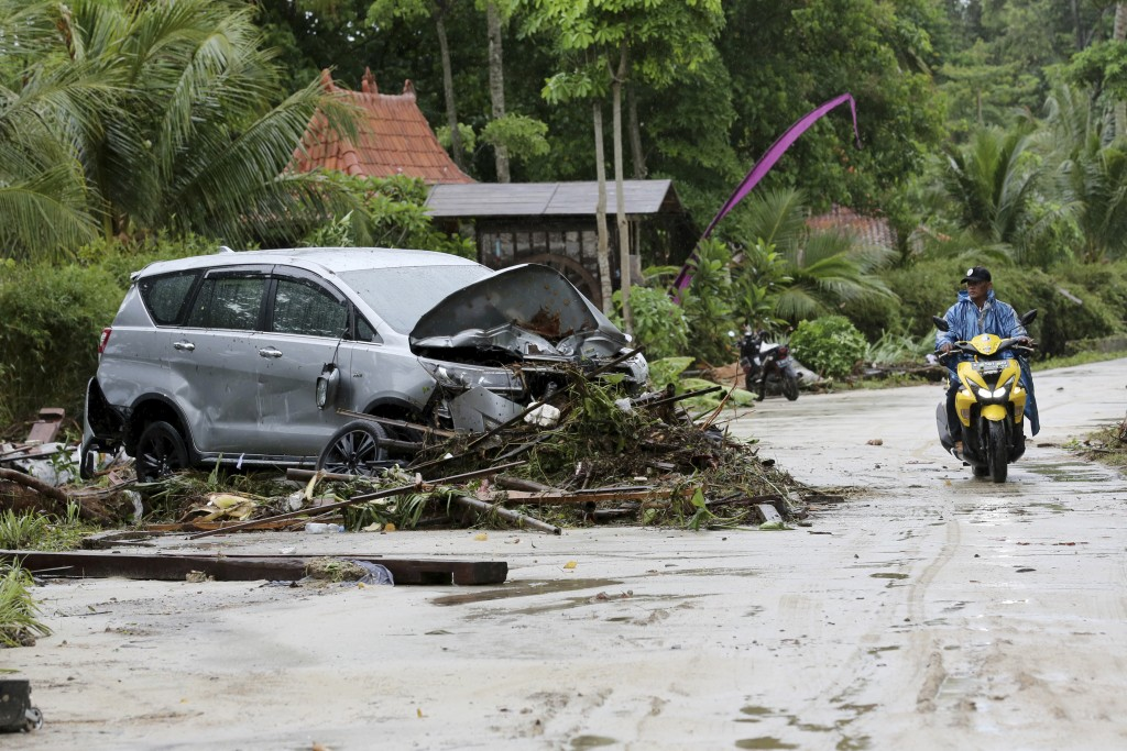 A motorist passes a car damaged by a tsunami, in Tanjung Lesung, Indonesia, Monday, Dec. 24, 2018. The tsunami apparently caused by the eruption of an