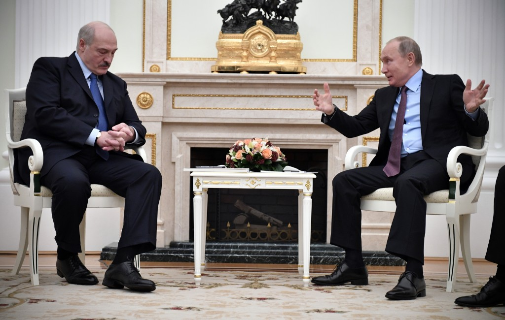 Russian President Vladimir Putin, right, gestures as he speaks to his Belarusian counterpart Alexander Lukashenko, foreground left, during their talks...