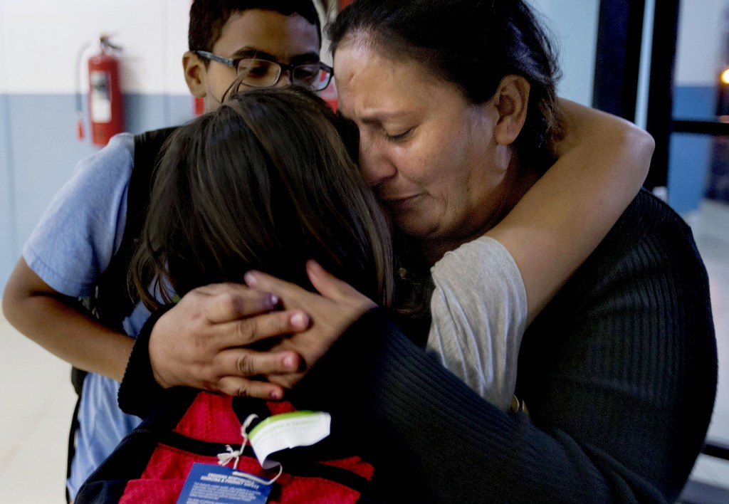 In this Oct. 17, 2018, photo, Maria Santiago Garcia hugs her two oldest children, Patrick and Sarai, goodbye at La Aurora International Airport in Gua...