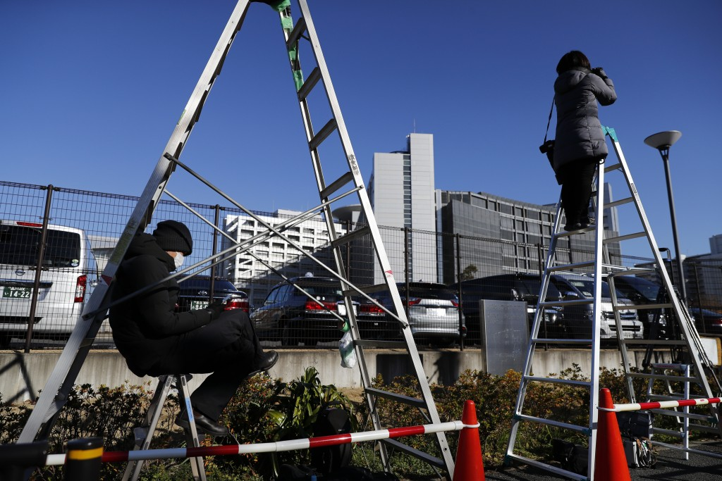 A TV crew and a photographer pause near Tokyo Detention Center, where former Nissan chairman Carlos Ghosn and another former executive Greg Kelly, are...