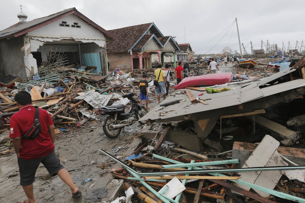 People inspect the damage at a tsunami-ravaged village in Sumur, Indonesia, Tuesday, Dec. 25, 2018. The Christmas holiday was somber with prayers for ...