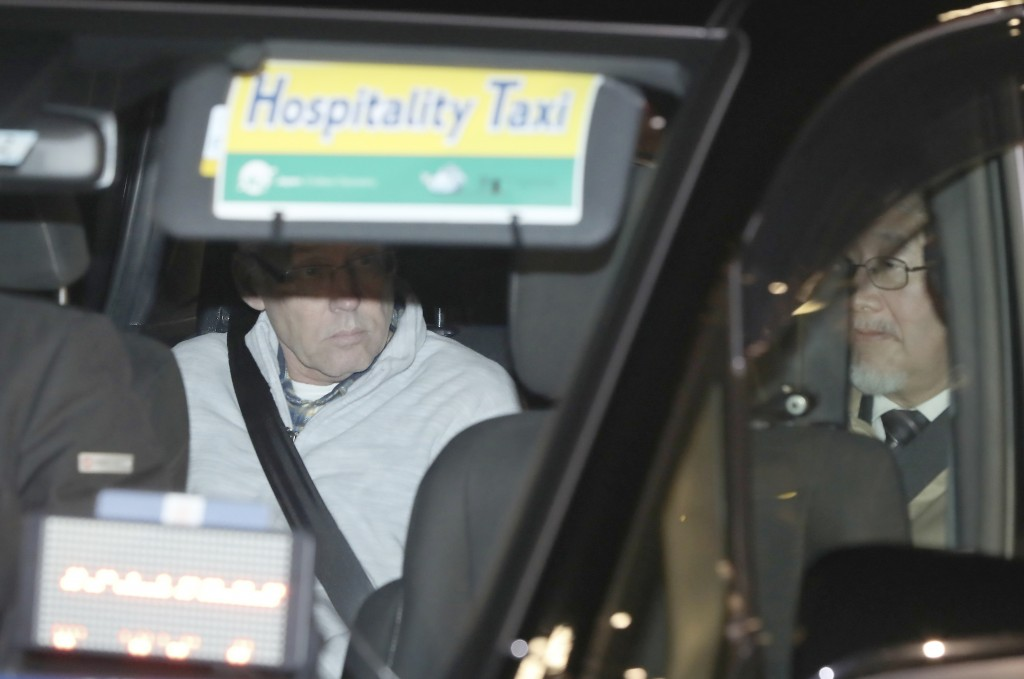 In this Tuesday, Dec. 25, 2018, file photo, a car carrying Nissan Motor Co.'s executive Greg Kelly, left, leaves Tokyo's Detention Center in Tokyo. Ni...