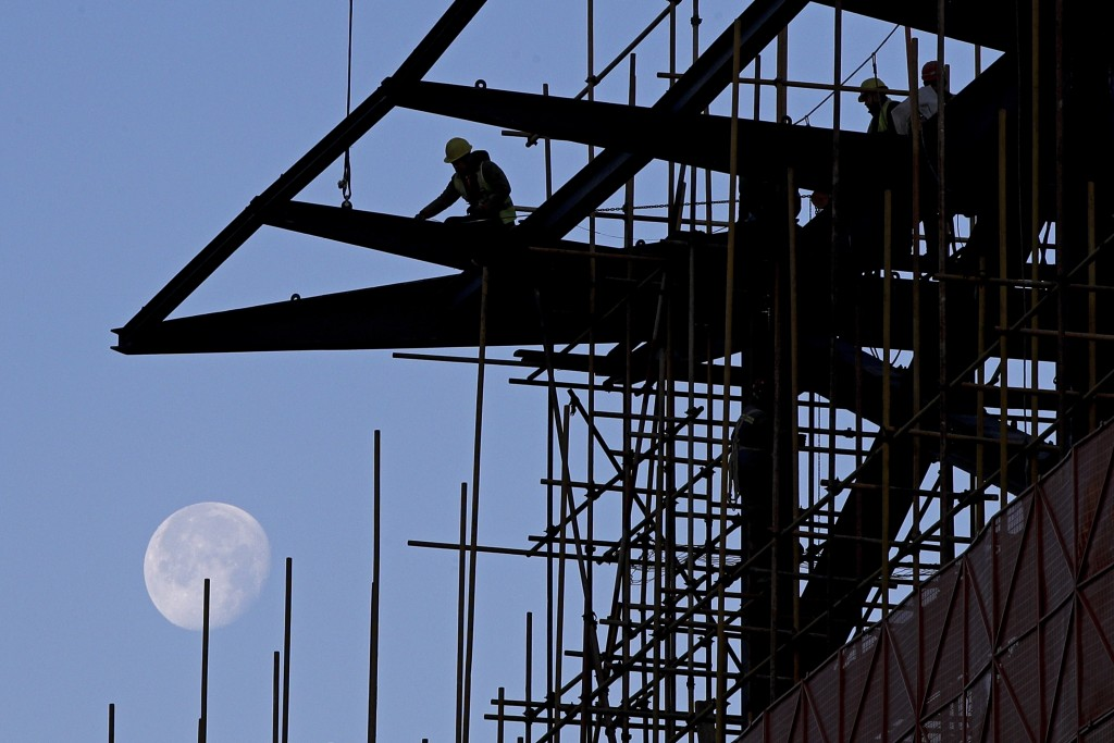 In this Tuesday, Dec. 25, 2018, file photo, workers load cables on a steel frames at a shopping mall under renovation, with a backdrop of the moon, in...