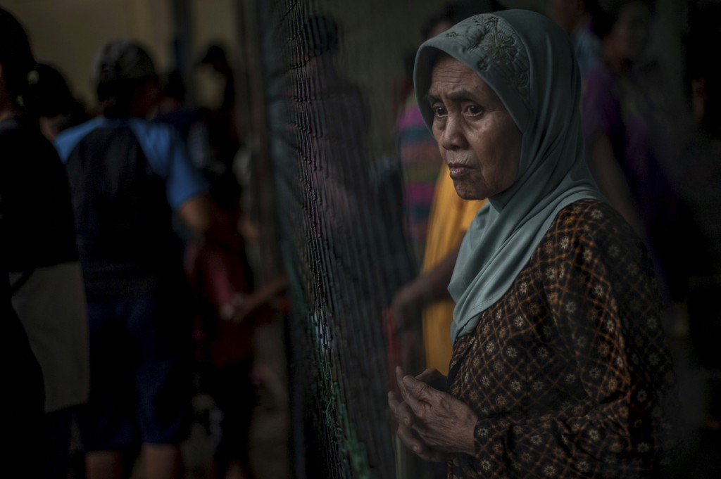 A survivor pauses at a temporary shelter for those affected by Saturday's tsunami in Carita, Indonesia, Tuesday, Dec. 25, 2018. Christmas celebrations