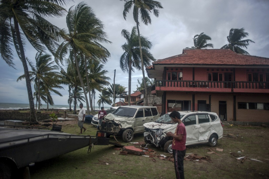 Owners reclaim their damaged cars from a resort affected by Saturday's tsunami in Carita, Indonesia, Tuesday, Dec. 25, 2018. Christmas celebrations tr
