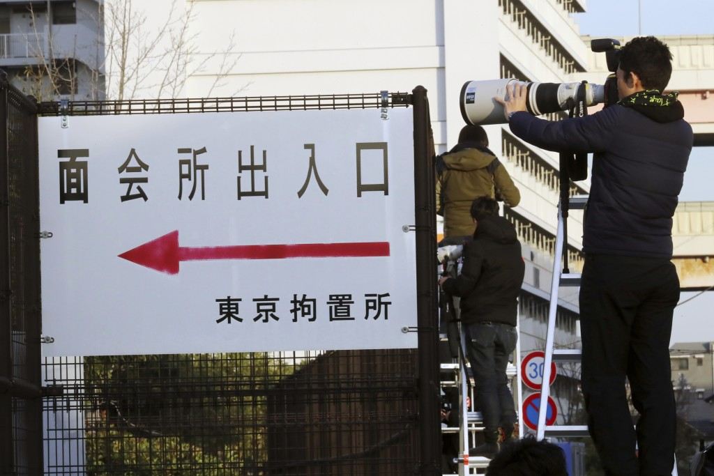 A photographer photographs toward Tokyo Detention Center, where former Nissan chairman Carlos Ghosn and another former executive Greg Kelly, are being...