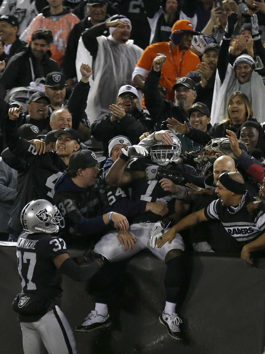 Oakland Raiders' Dwayne Harris, center, celebrates with fans after returning a punt for a touchdown against the Denver Broncos during the first half o...