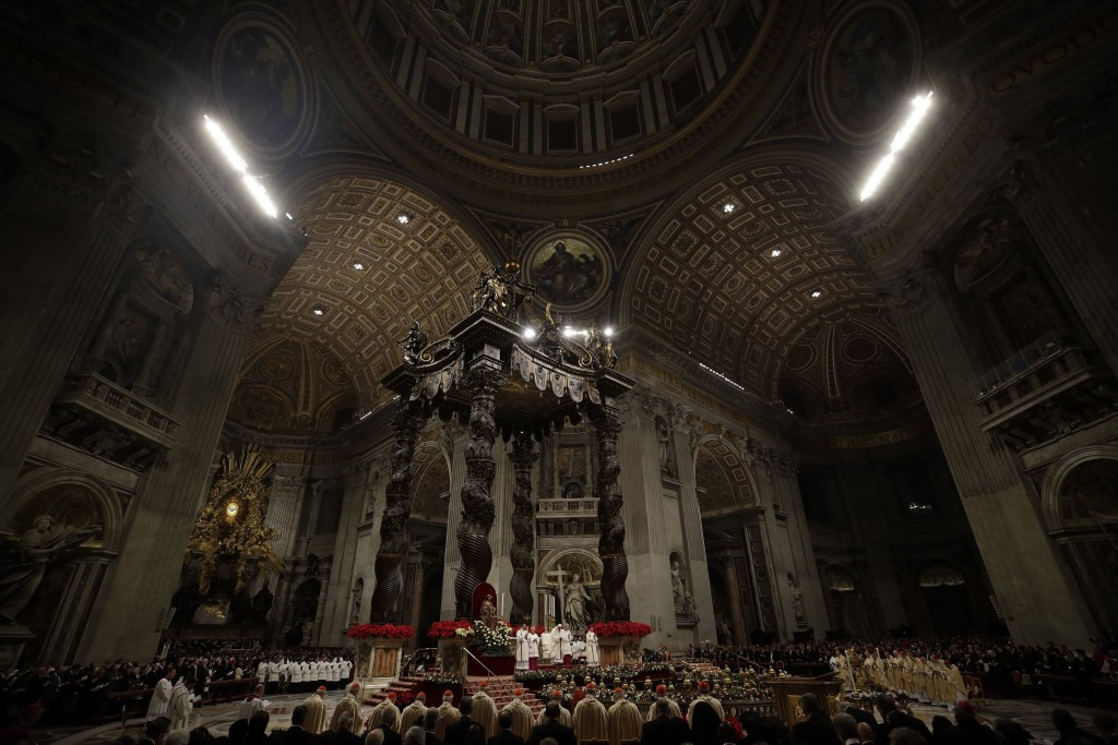 Faithful and prelates gather in front of the altar during the Christmas Eve Mass celebrated by Pope Francis in St. Peter's Basilica at the Vatican, Mo...