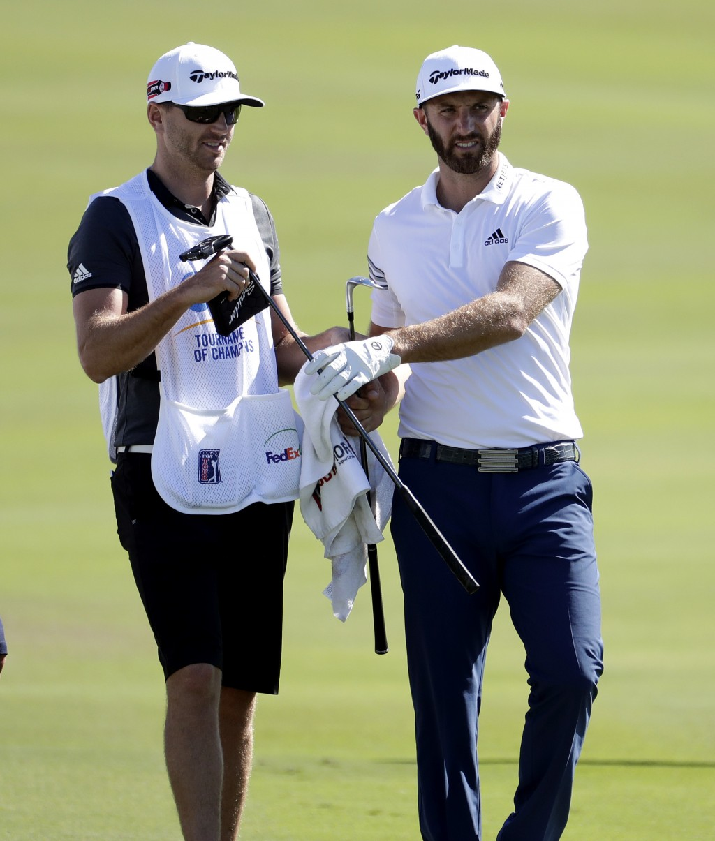 FILE - In this Jan. 4, 2017, file photo, Dustin Johnson, right, exchanges clubs with his caddy, brother Austin Johnson, on the 18th green during the p...