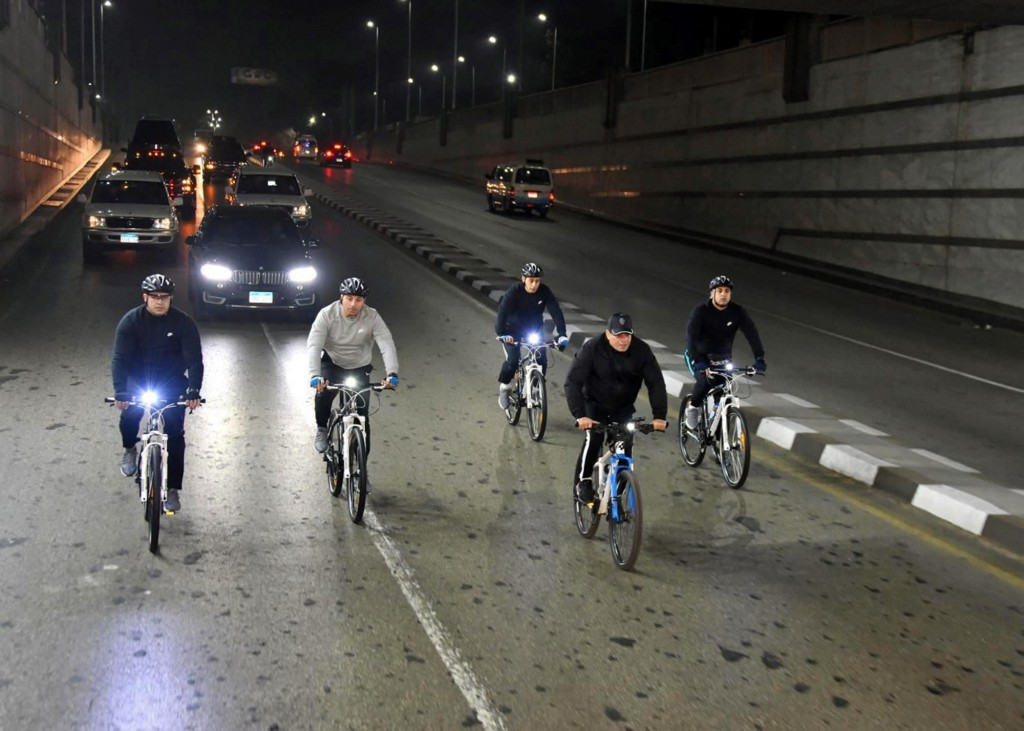 In this Dec. 16, 2018 photo released by the Egyptian Presidency, Egyptian President Abdel-Fattah el-Sissi rides his bike to the national Military Acad...