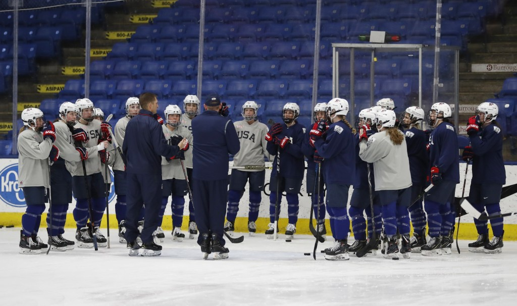 In a photo from, Thursday, Dec. 20, 2018, in Plymouth, Mich., members of the USA Hockey women's team listen to their coach during practice. After thre...