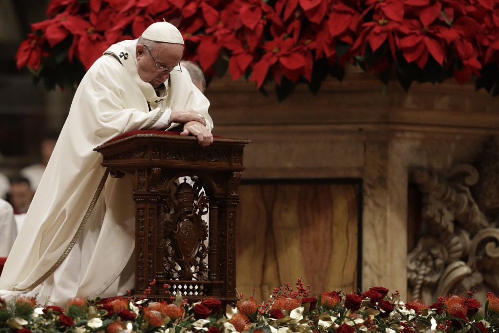 Pope Francis kneels on the altar as he celebrates the Christmas Eve Mass in St. Peter's Basilica at the Vatican, Monday, Dec. 24, 2018. (AP Photo/Ales...