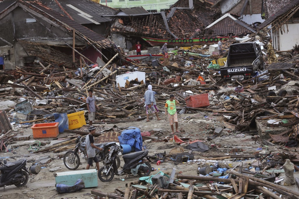 In this Tuesday, Dec. 25, 2018, file photo, people inspect the damage at a tsunami-ravaged village in Sumur, Indonesia. The Christmas holiday was somb...