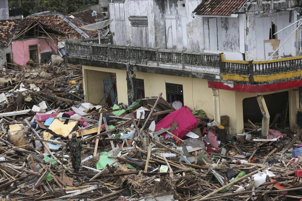 An Indonesian soldier inspects the damage at a tsunami-ravaged village in Sumur, Indonesia, Tuesday, Dec. 25, 2018. The Christmas holiday was somber w...