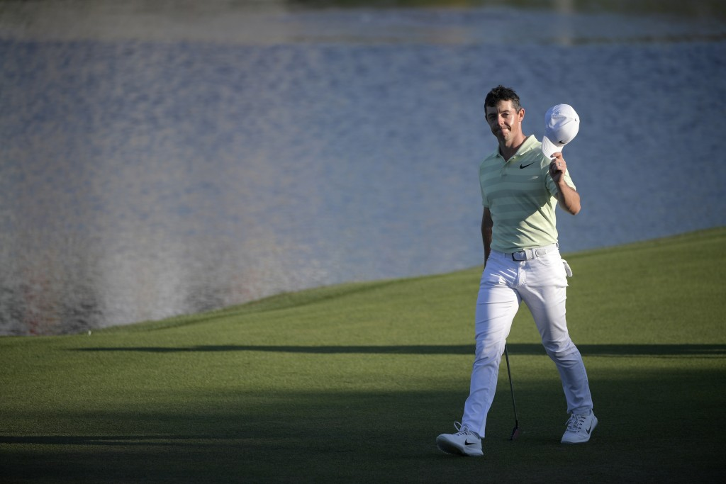FILE - In this March 18, 2018, file photo, Rory McIlroy, of Northern Ireland, waves his hat to the crowd while walking to his ball on the 18th green d...