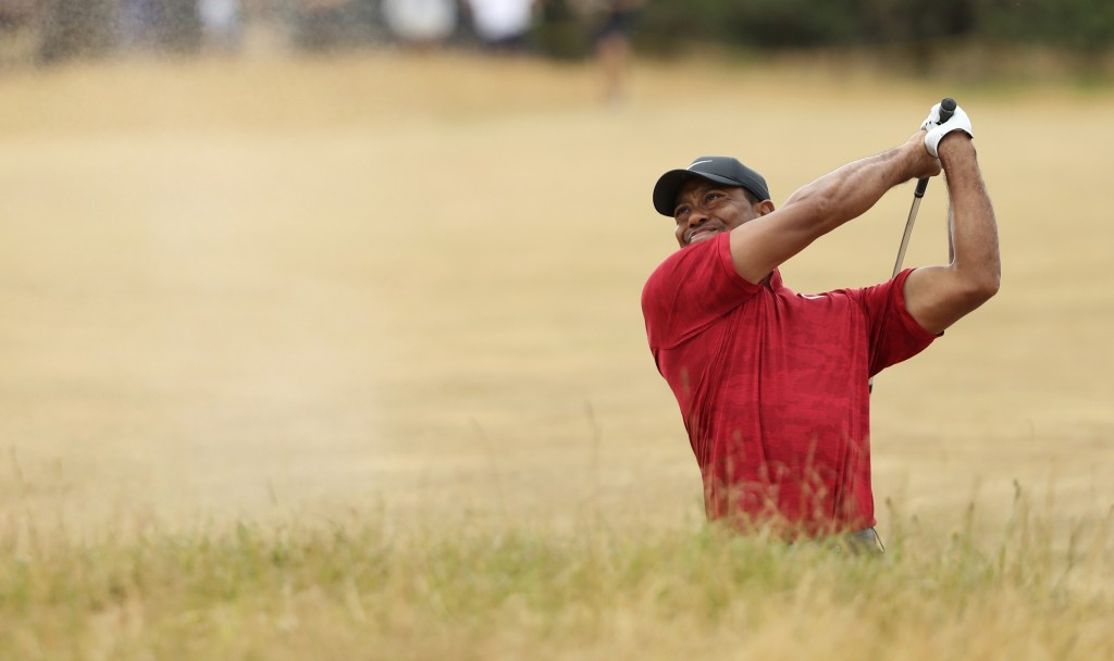 FILE - In this July 22, 2018, file photo, Tiger Woods of the U.S. plays out of a bunker on the 10th hole during the final round for the 147th British ...