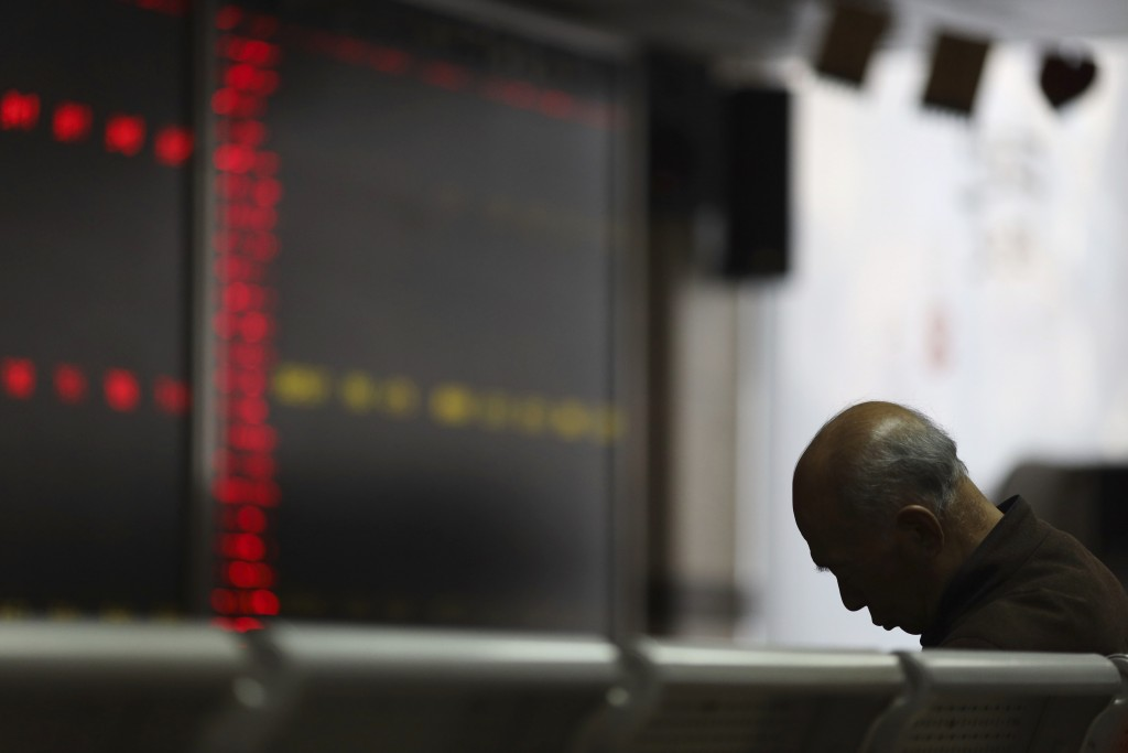 A Chinese man naps at a brokerage in Beijing, China, Tuesday, Dec. 25, 2018. Japanese stocks plunged Tuesday and other Asian markets declined followin...