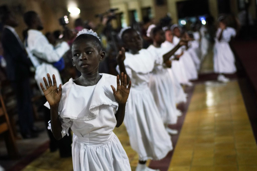 Congolese children dance before Msg. Fridolin Ambongo, the the newly appointed Archibishop of Kinshasa, delivers the homily during an early midnight m...