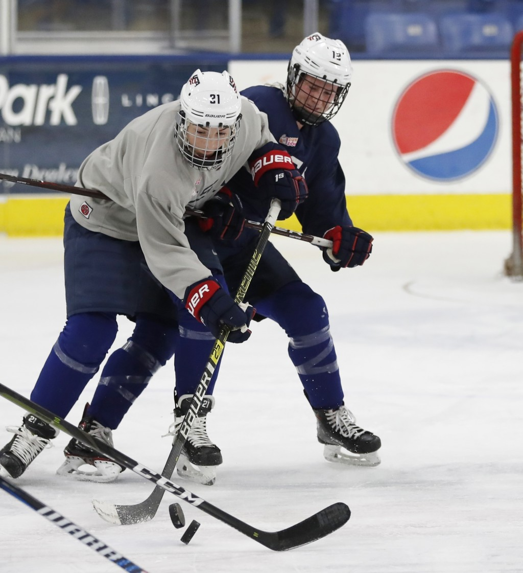 In a photo from, Thursday, Dec. 20, 2018, in Plymouth, Mich., USA Hockey forwards Hilary Knight, left, and Kelly Panneck chase the pucks during practi...