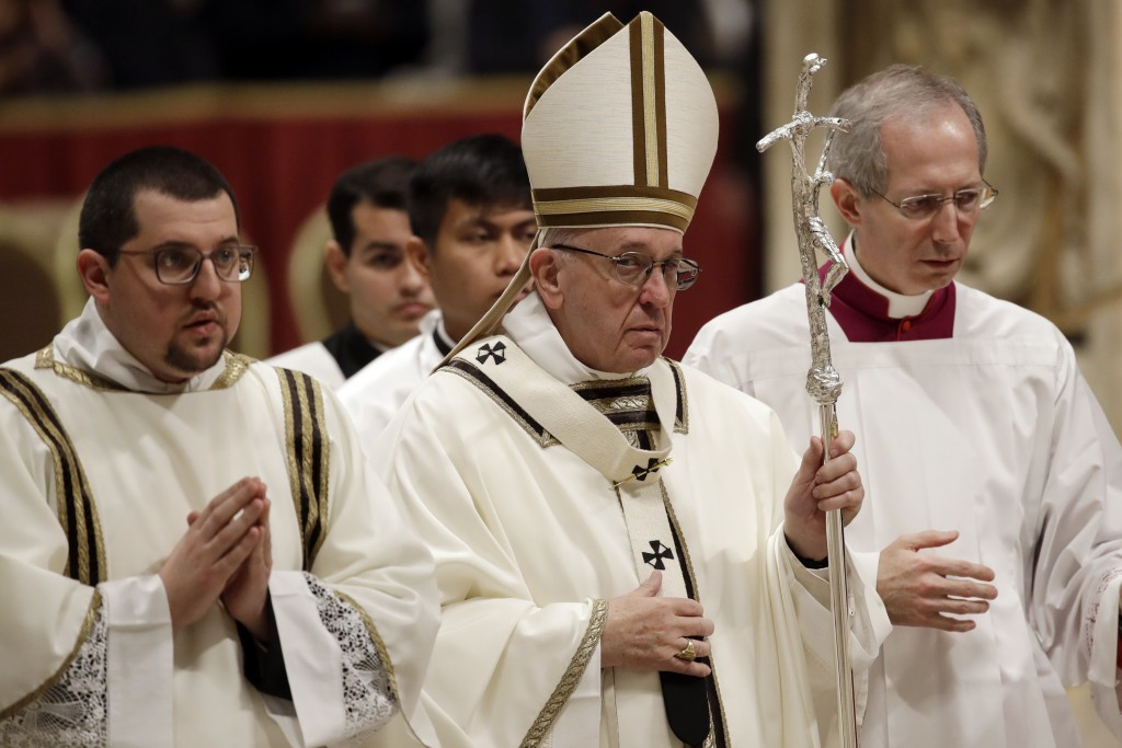 Pope Francis walks with the pastoral staff as he leaves at the end of the Christmas Eve Mass in St. Peter's Basilica at the Vatican, Monday, Dec. 24, ...
