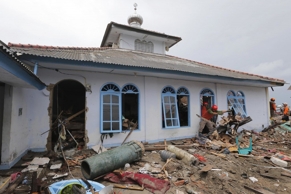 People clean up a mosque following the tsunami in Sumur, Indonesia, Tuesday, Dec. 25, 2018. The Christmas holiday was somber with prayers for tsunami ...