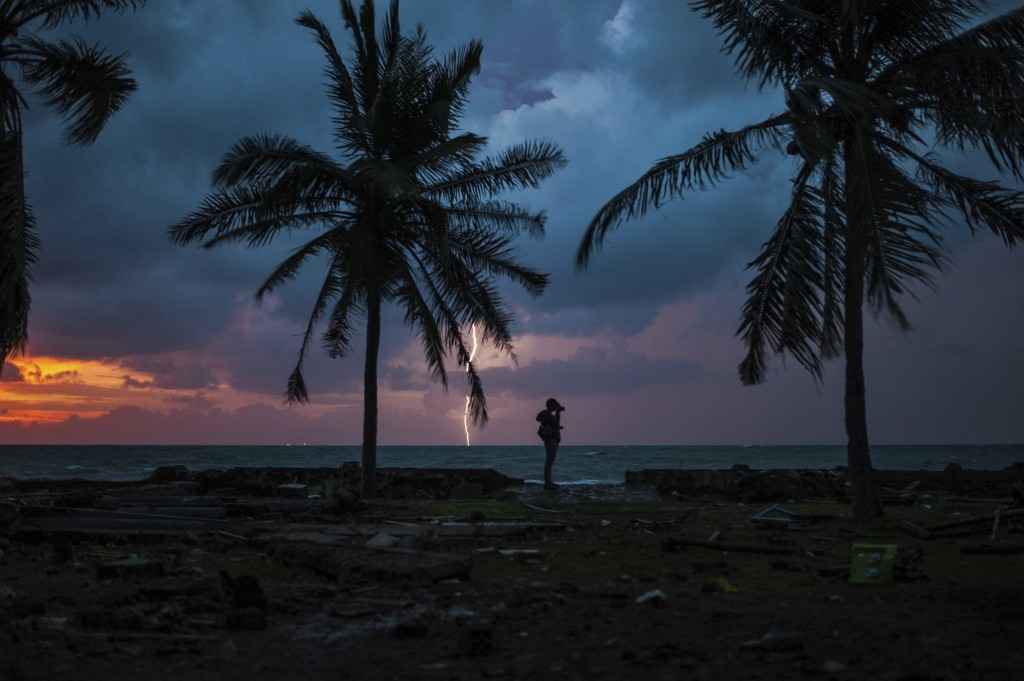 In this Tuesday, Dec. 25, 2018, file photo, a photojournalist is silhouetted by the sunset as a lightning strike at a resort affected by Saturday's ts...