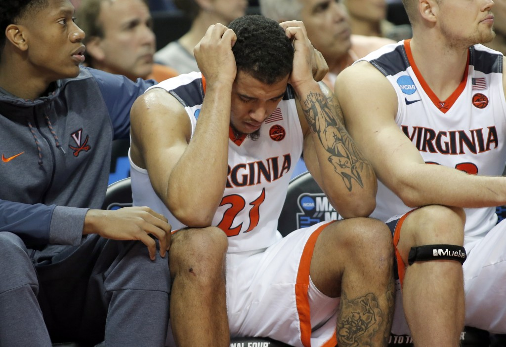 FILE - In this March 16, 2018, file photo, Virginia's Isaiah Wilkins (21) is consoled after fouling out in the second half of the team's first-round g...
