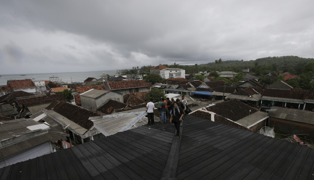 People feared by tsunami take shelter on the top of a mosque in Sumur village , Indonesia, Tuesday, Dec. 25, 2018. The Christmas holiday was somber wi...