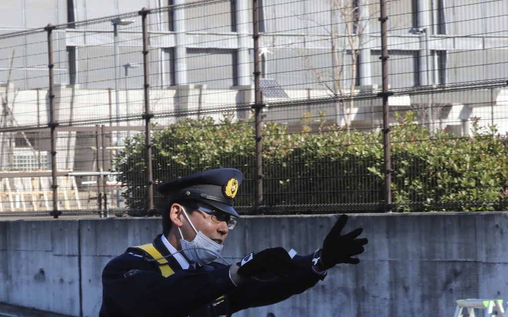 A police officer gestures in front of the gate of Tokyo Detention Center, where former Nissan chairman Carlos Ghosn and another former executive Greg ...