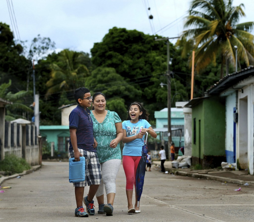 In this Oct. 15, 2018, photo, Patrick, his mother Maria Santiago Garcia, and his sister Sarai, walk home in Jerez, Guatemala. Garcia, a Guatemalan wom...