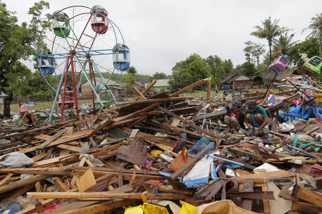 People collect usable items in debris, following Saturday's tsunami in Sumur, Indonesia, Tuesday, Dec. 25, 2018. The Christmas holiday was somber with