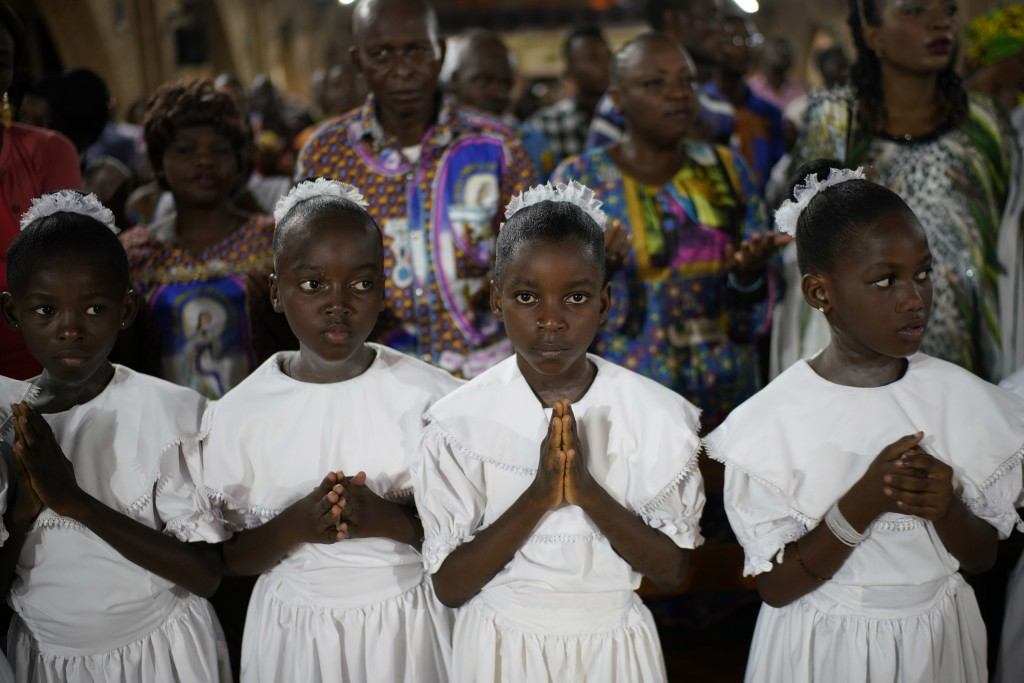 Congolese children pray as Msg. Fridolin Ambongo, the the newly appointed Archibishop of Kinshasa, delivers the homily during an early midnight mass a...