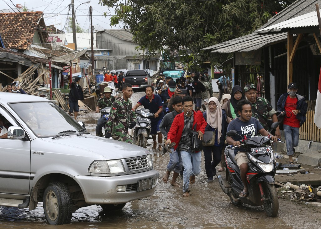 People feared by tsunami run in panic on a street in Sumur village , Indonesia, Tuesday, Dec. 25, 2018. The Christmas holiday was somber with prayers ...