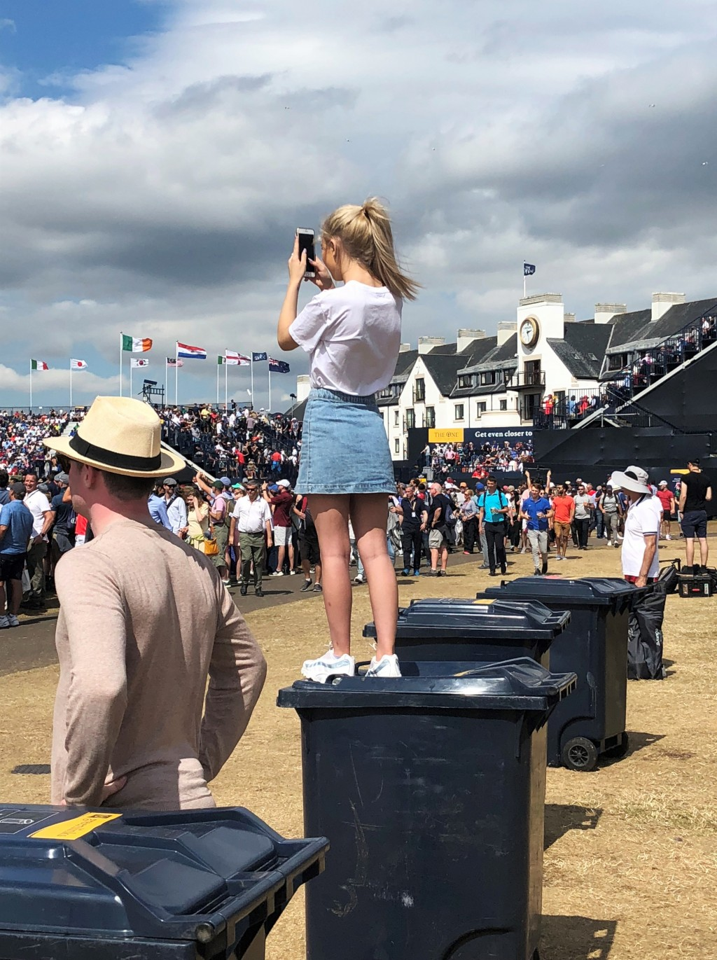In this July 22, 2018 photo, a young girl stands atop a trash bin to catch a glimpse of Tiger Woods as he tees off in the final round of the British O...