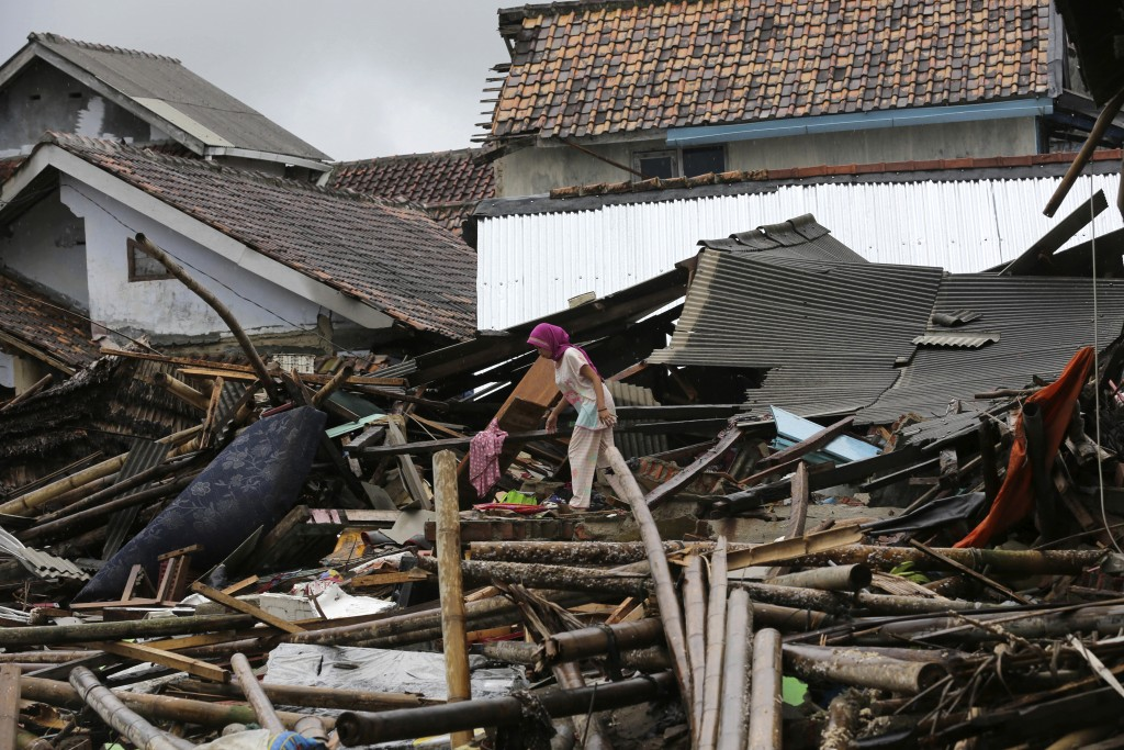 A woman walks on the debris following the tsunami in Sumur, Indonesia, Tuesday, Dec. 25, 2018. The Christmas holiday was somber with prayers for tsuna...
