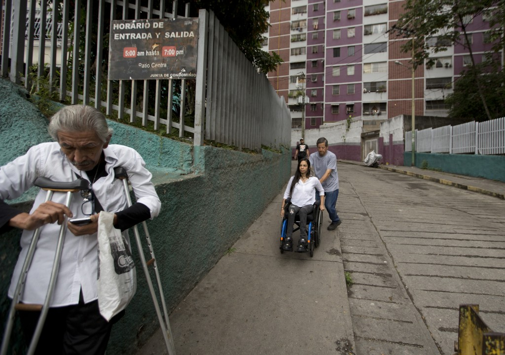 In this Dec. 17, 2018 photo, neighbor Dixon Rosales helps dancer Iraly Yanez negotiate her wheelchair on a downhill path, in Caracas, Venezuela. A str...