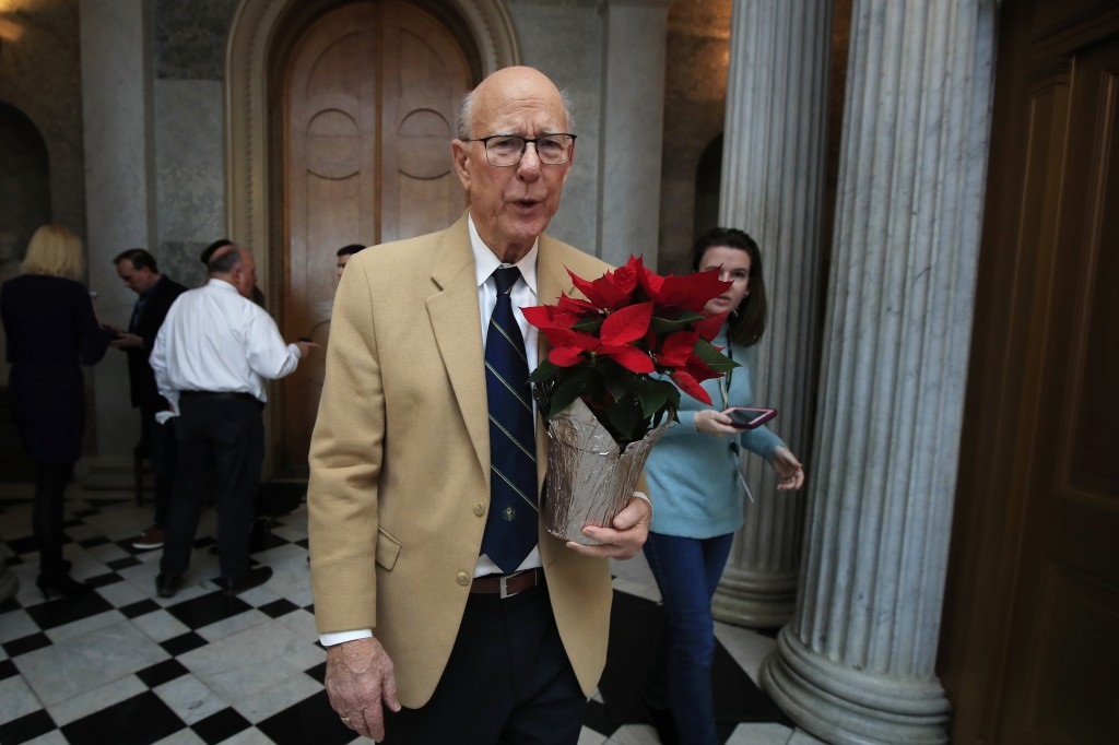 Sen. Pat Roberts, R-Kan., carries a poinsettia on Capitol Hill in Washington, Monday, Dec. 24, 2018, after a pro forma session, a brief meeting of the...