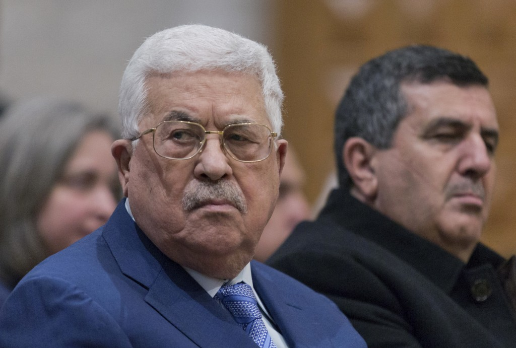 Palestinian President Mahmoud Abbas, left, attends a Christmas midnight mass at Saint Catherine's Church, in the Church of the Nativity, traditionally