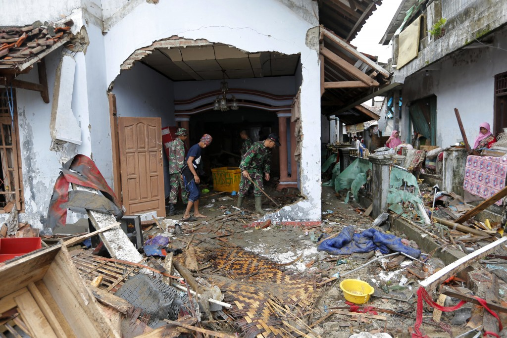 Indonesian soldiers and people clean up the debris following the tsunami in Sumur, Indonesia, Tuesday, Dec. 25, 2018. The Christmas holiday was somber