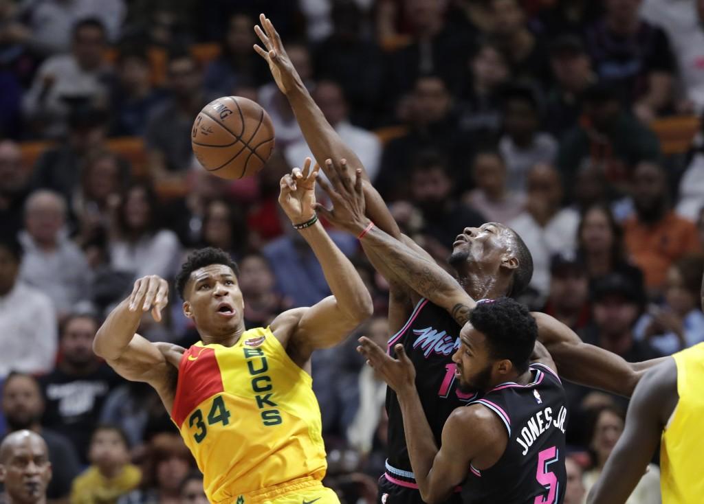 FILE - In this Dec. 22, 2018, file photo, Milwaukee Bucks forward Giannis Antetokounmpo (34) passes as Miami Heat center Bam Adebayo, center, and forw...