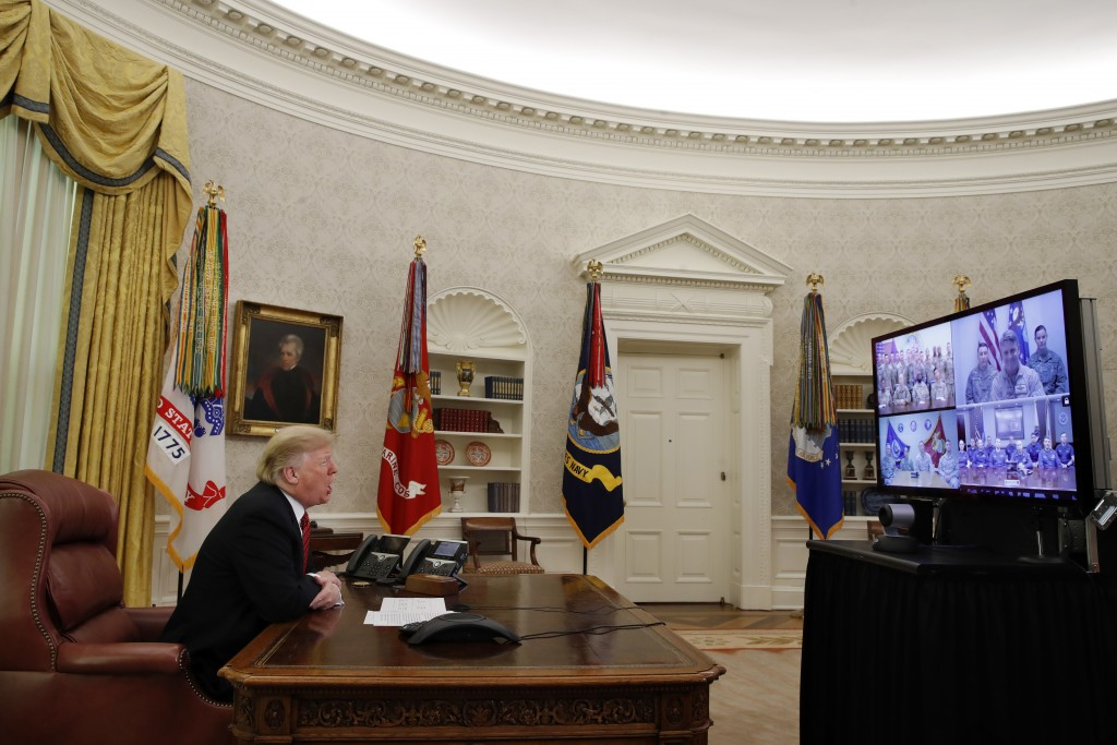 President Donald Trump greets members of the five branches of the military via video conference on Christmas Day, Tuesday, Dec. 25, 2018, in the Oval ...