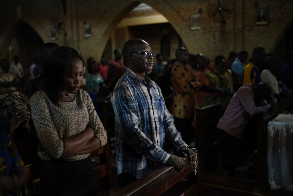 Congolese worshipers listen to Msg. Fridolin Ambongo, the the newly appointed Archibishop of Kinshasa, deliver the homily during an early midnight mas...