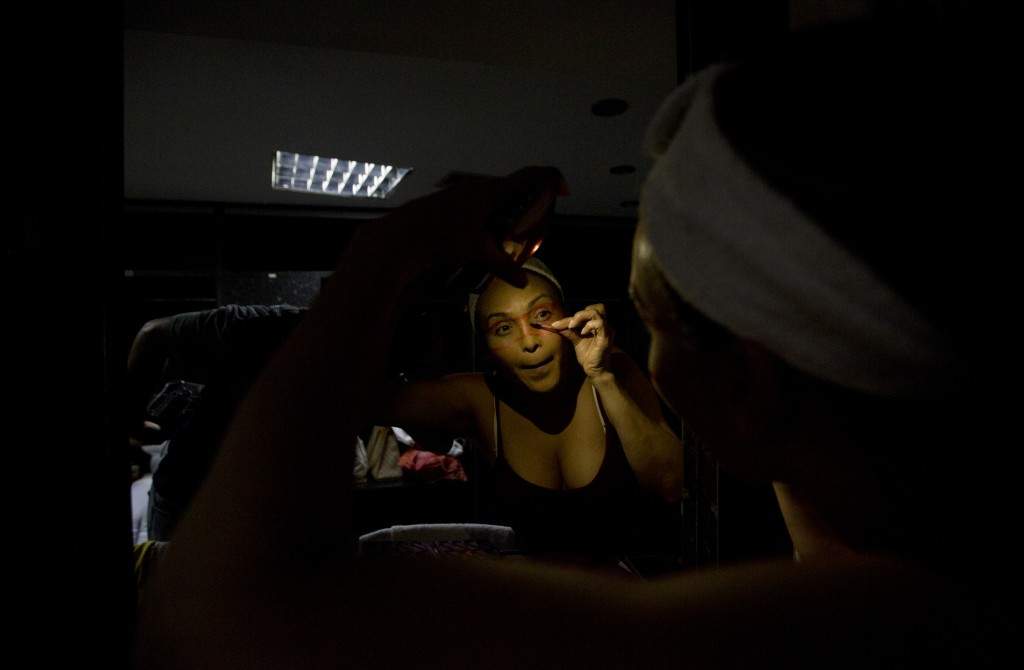 In this Dec. 4, 2018 photo, dancer Morelis Silva uses a cell phone to provide illumination to apply makeup in preparation for the contemporary dance p...