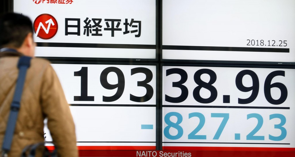 CORRECTS DATE - A man looks at the day's loss of Nikkei stock index on an electronic stock board at a securities firm in Tokyo, Tuesday, Dec. 25, 2018...