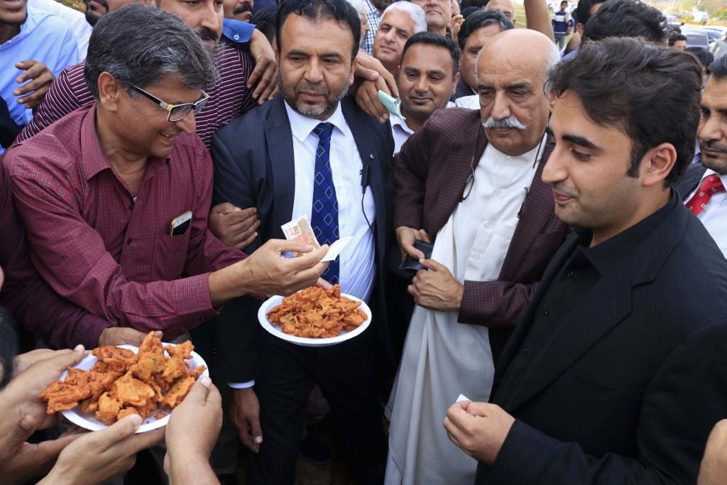 In this Oct. 30, 2018 photo, Pakistani journalist Shakil Anjum, left, sells food with his jobless colleagues to opposition leader Bilawal Bhutto, righ...