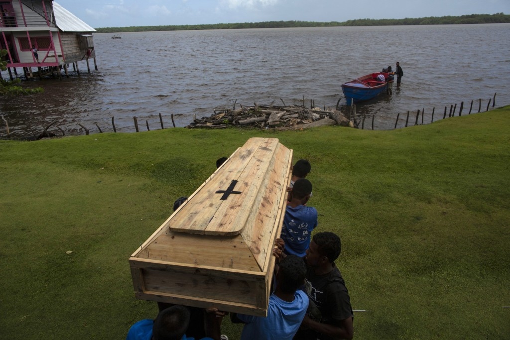 In this Sept. 2, 2018 photo, relatives and friends carry the coffin that contains the remains of Miskito diver Oscar Salomon Charly, 31, to be transpo...
