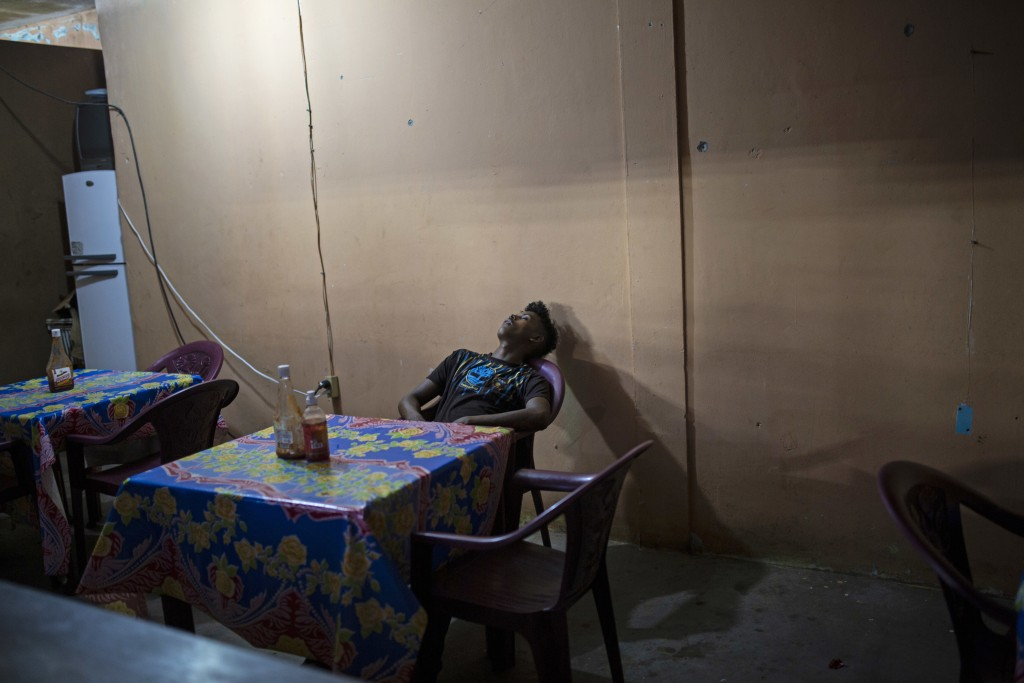 In this Feb. 9, 2018 photo, a man takes a nap inside a makeshift restaurant in Puerto Lempira, Honduras. With more than 60 per cent of its 9 million p...